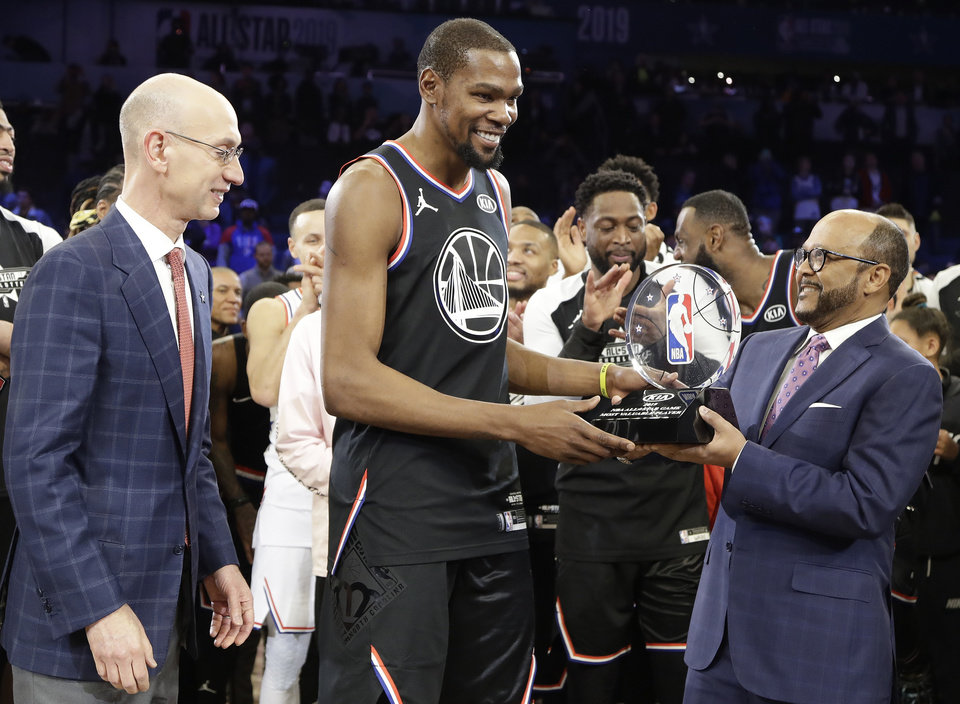 Photo - Team LeBron's Kevin Durant, of the Golden State Warriors receives the MVP trophy after the NBA All-Star basketball game as NBA commissioner Adam Silver, left, looks on Sunday, Feb. 17, 2019, in Charlotte, N.C. The Team LeBron won 178-164. (AP Photo/Chuck Burton)