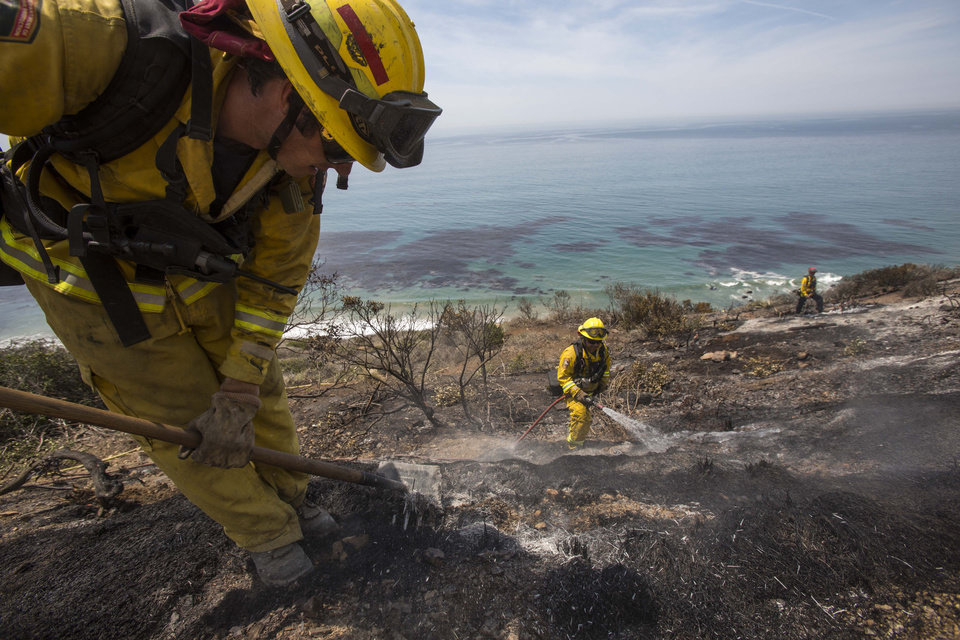 Firefighters work on the burned area along the Pacific Coast Highway, in Point Mugu, Calif., Friday, May 3, 2013. A huge wildfire carved a path to the sea and burned on the beach Friday, but firefighters got a break as gusty winds turned into breezes. Temperatures remained high, but humidity levels were expected to soar as cool air moved in from the ocean and the Santa Ana winds retreated. (AP Photo/Ringo H.W. Chiu) ORG XMIT: CARC122