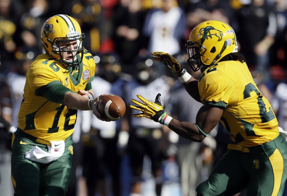Photo - North Dakota State quarterback Brock Jensen (16) hands the ball off to running back Sam Ojuri (22) in the first half of the FCS championship NCAA college football game against Towson, Saturday, Jan. 4, 2014, in Frisco, Texas. (AP Photo/Tony Gutierrez)
