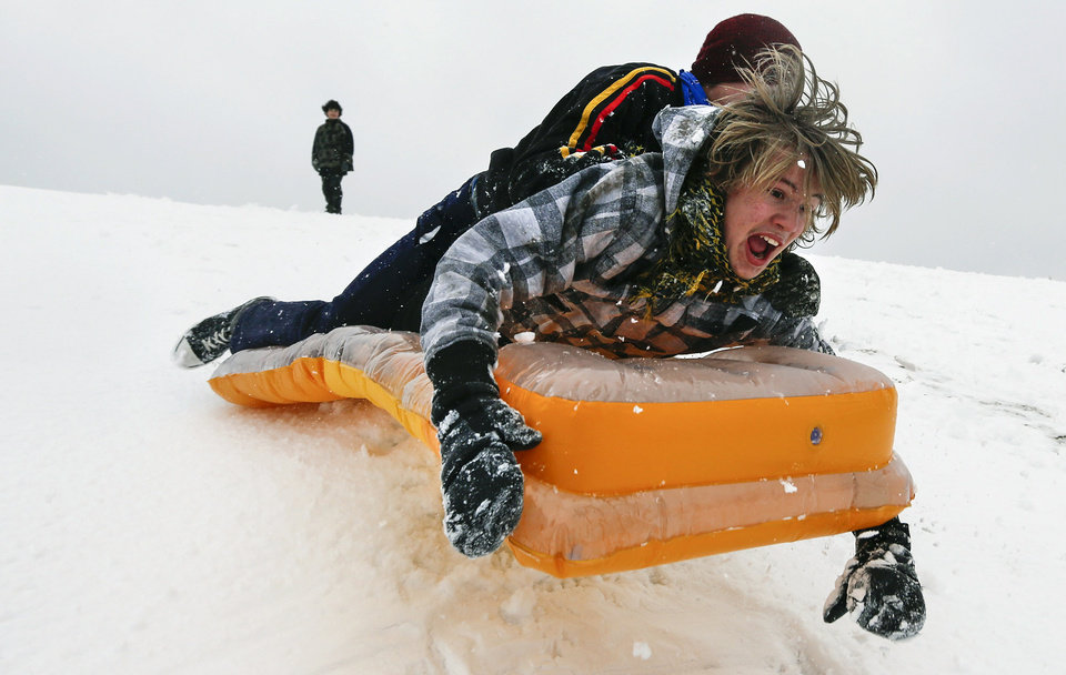 Photo - Simon Mourning, bottom, and Chance Cain sled  near downtown Wichita, Kan. as a winter storm moves through the area on Monday, Feb. 25, 2013. (AP Photo/The Wichita Eagle, Travis Heying) LOCAL TV OUT; MAGS OUT; LOCAL RADIO OUT; LOCAL INTERNET OUT