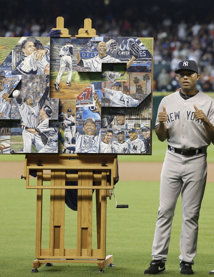 Photo - Retiring New York Yankees relief pitcher Mariano Rivera gives a thumbs up to a painting presented to him during a ceremony before a baseball game against the Houston Astros Sunday, Sept. 29, 2013, in Houston. (AP Photo/Richard Carson)