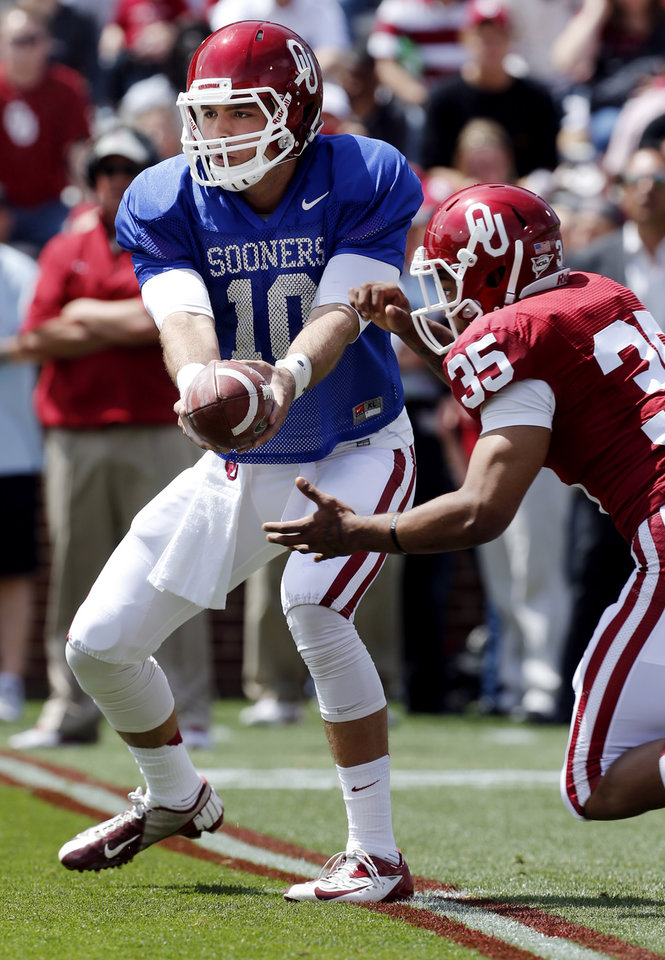 Photo - Quarterback Blake Bell hands off to Terence Olds (35) during the annual Spring Football Game at Gaylord Family-Oklahoma Memorial Stadium in Norman, Okla., on Saturday, April 13, 2013. Photo by Steve Sisney, The Oklahoman