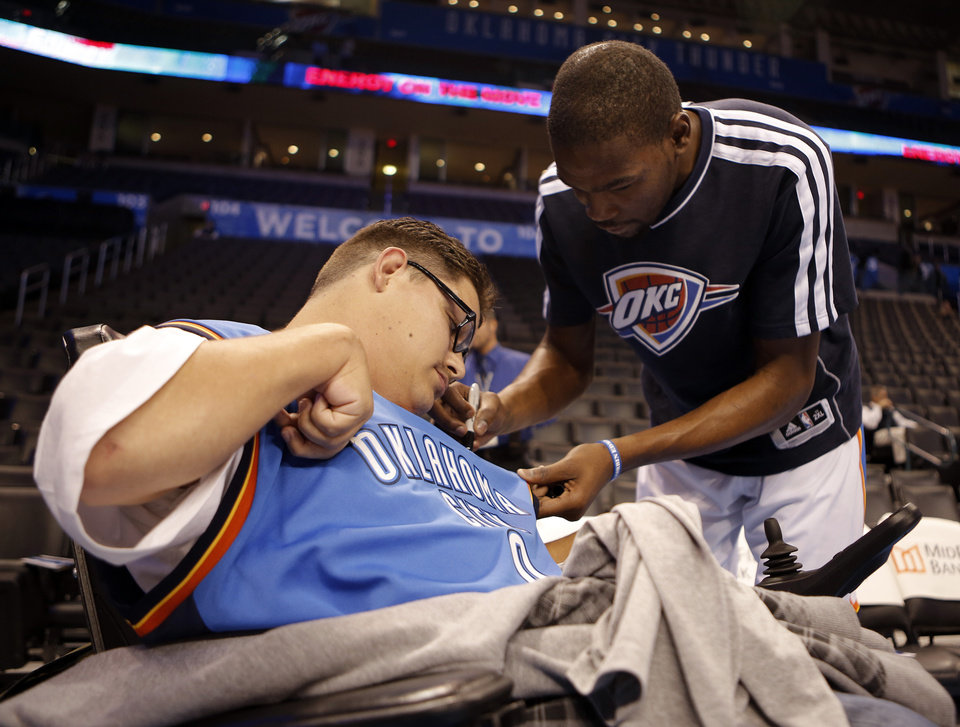 Photo - FANS: Kevin Durant signs  Andrew Rains shirt before an NBA basketball game between the Oklahoma City Thunder and the Golden State Warriors at Chesapeake Energy Arena in Oklahoma City, Sunday, Nov. 18, 2012.  Andrew Rains suffers from cerebral palsy, and is attending his first Thunder game.  He never misses a game on television.  Photo by Garett Fisbeck, The Oklahoman