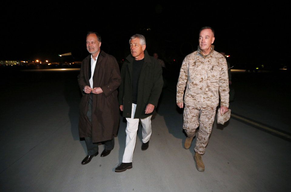 Photo - U.S. Secretary of Defense Chuck Hagel walks with U.S. Ambassador to Afghanistan James Cunningham, left, and Gen. Joseph Dunford, Commander of the International Security Force, upon Hagel's arrival in Kabul, Afghanistan, Friday, March 8, 2013. This is Hagel's first official trip since being sworn-in as Obama's Defense Secretary. (AP Photo/Jason Reed, Pool)