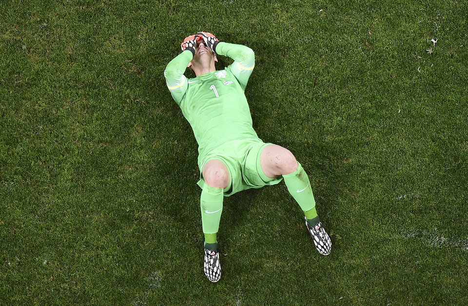 Photo - Netherlands' goalkeeper Jasper Cillessen lies on the pitch after losing to Argentina in a World Cup semifinal soccer match at the Itaquerao Stadium in Sao Paulo, Brazil, Wednesday, July 9, 2014. Argentina beat the Netherlands 4-2 in a penalty shootout to reach the World Cup final against Germany. (AP Photo/Francois Xavier Marit, Pool)