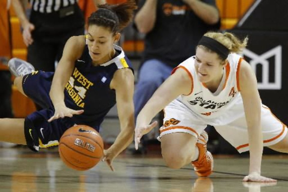 West Virginia's Jess Harlee , left, and Oklahoma State's Liz Donohoe dive for a loose ball during the Mountaineers' win in Stillwater. PHOTO BY BRYAN TERRY, THE OKLAHOMAN