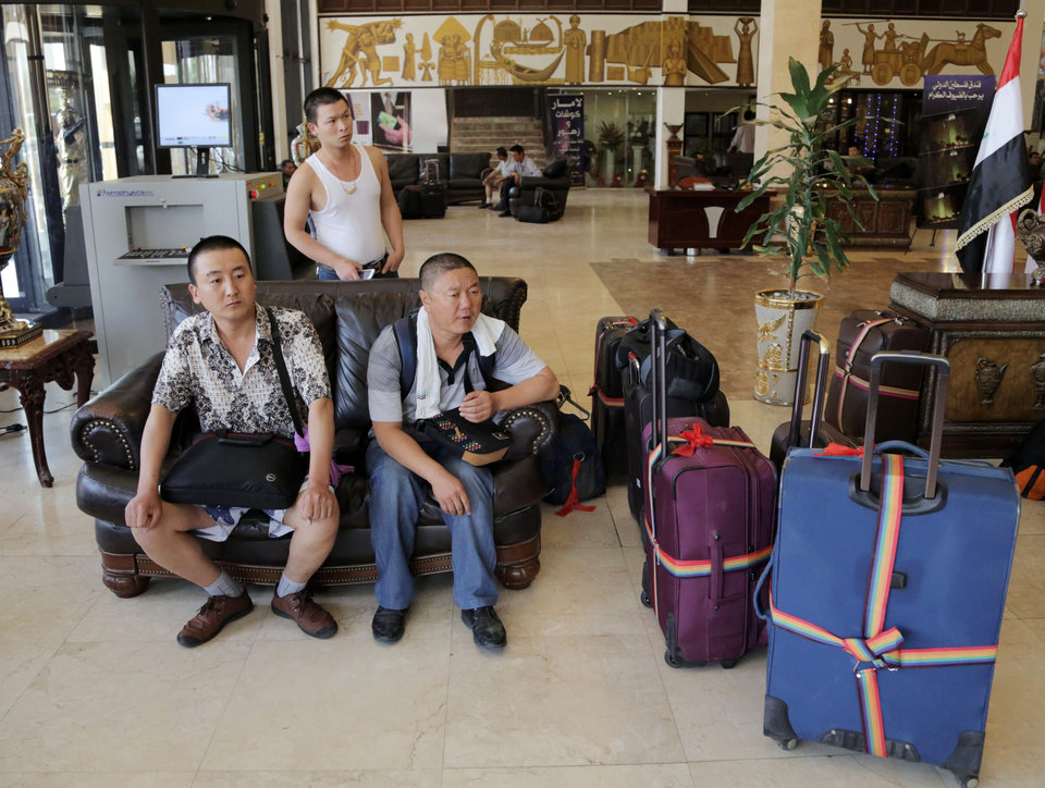 Photo - Chinese workers who fled from Samarra, Iraq, wait for buses to begin their journey home as they sit at a hotel in Baghdad, Iraq, Saturday, June 28, 2014. China's official Xinhua news agency said that more than 1,200 Chinese workers who had been trapped in the embattled northern Iraqi city of Samarra have been evacuated safely to Baghdad, with the Iraqi military providing security. (AP Photo/Khalid Mohammed)