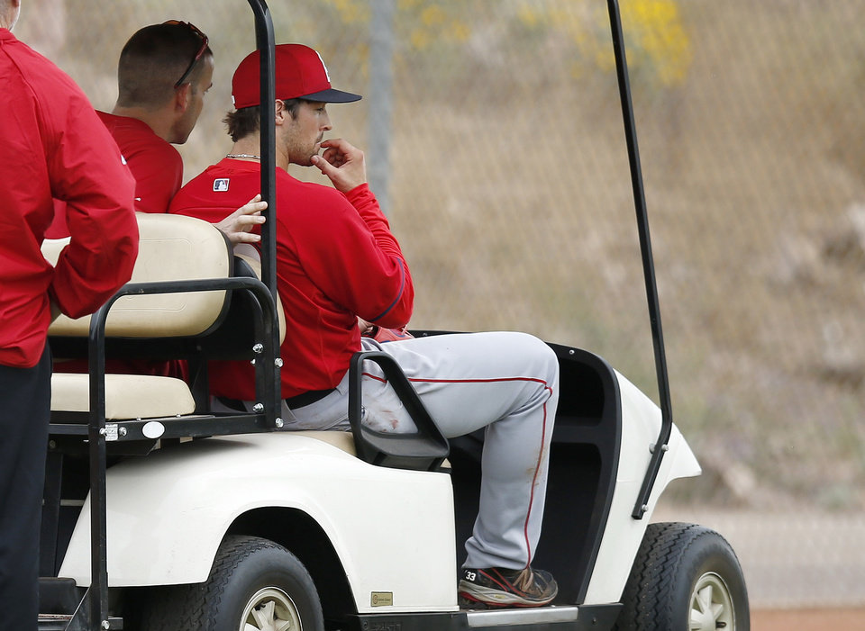 Photo - Los Angeles Angels' C.J. Wilson, right, is taken back to the clubhouse by medical personnel after being struck in the head with a line drive while he was pitching during spring training baseball practice on Tuesday, Feb. 25, 2014, in Tempe, Ariz. (AP Photo/Ross D. Franklin)