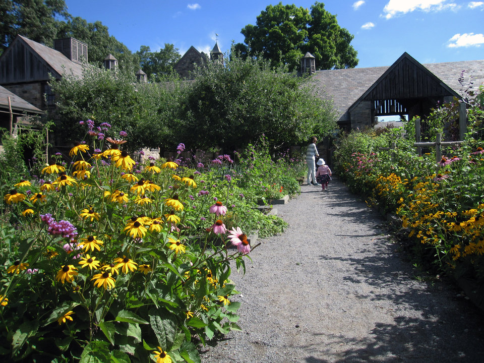 Photo - In this Aug. 15, 2014, photo, visitors walk through a flower garden at Stone Barns, a nonprofit working farm in Pocantico Hills, N.Y., dedicated to education and conservation. Stone Barns belonged to the Rockefeller family and was turned into an education site by David Rockefeller in honor of his late wife Peggy, an advocate for farmland preservation. Visitors can see organic gardens, greenhouses, free-range turkeys and chickens, a barn full of piglets, fields of vegetables, and a buzzing apiary.(AP Photo/Beth J. Harpaz)