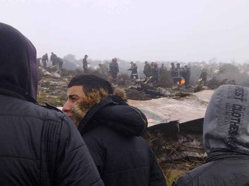 Photo - People watch rescue workers working at the wreckage of an Algerian military transport aircraft after it slammed into a mountain in the country's rugged eastern region, Tuesday, Feb. 11, 2014. A civil defense official said 102 people on board were killed but one person managed to survive. The U.S.-built C-130 Hercules transport crashed about noon near the town of Ain Kercha, 50 kilometers (30 miles) southeast of Constantine, the main city in eastern Algeria. ( AP Photo/ Mohamed Ali)