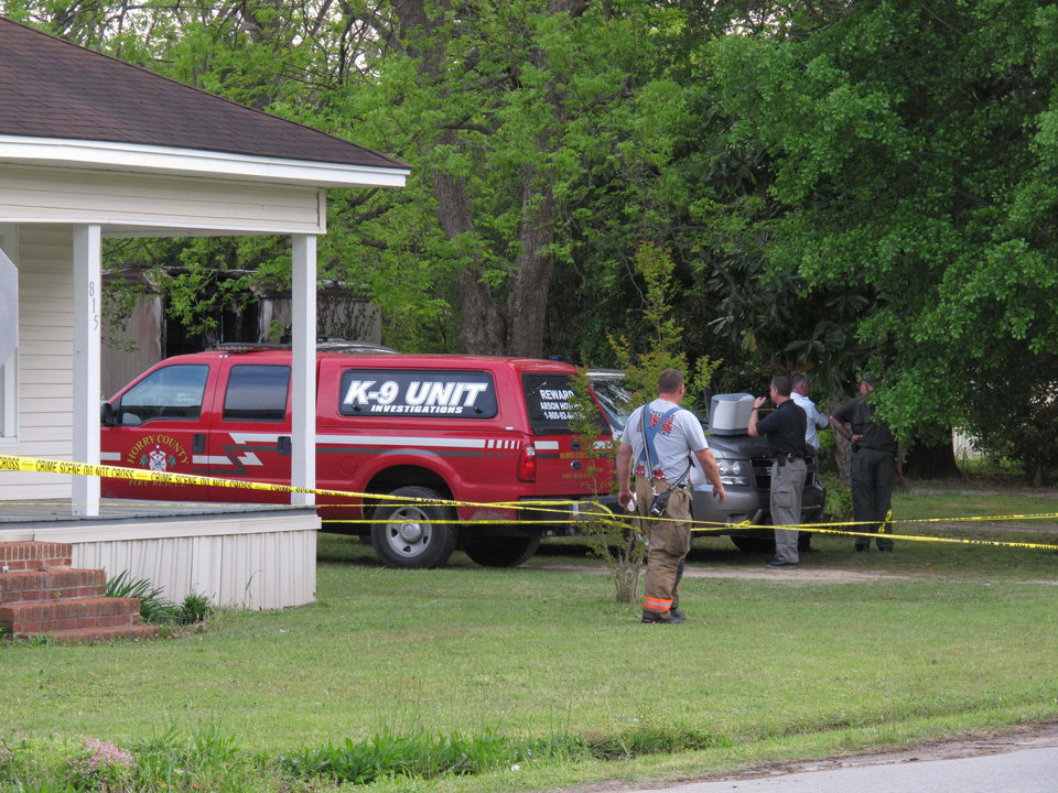 Photo - Investigators gather at the scene of a fatal fire on Wednesday, April 24, 2013, in Hartsville, S.C. Four young children, including twin girls, perished when fire swept through a mobile home. (AP Photo/Jeffrey Collins)