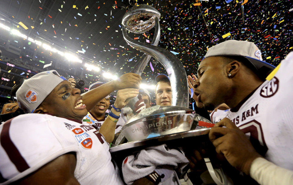Photo - Texas A&M defensive backs Tramain Jacobs, left, and Steven Terrell celebrate with the trophy after the Cotton Bowl NCAA college football game against Oklahoma Friday, Jan. 4, 2013, in Irving, Texas. Texas A&M  won 41-13. (AP Photo/LM Otero)