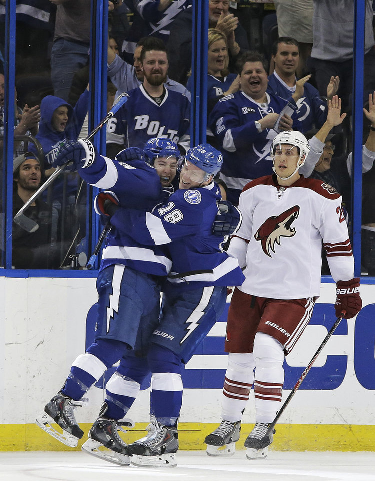Photo - Tampa Bay Lightning center Tyler Johnson (9) celebrates his goal against the Phoenix Coyotes with teammate Ondrej Palat (18), of the Czech Republic, during the first period of an NHL hockey game, Monday, March 10, 2014, in Tampa, Fla. Skating off is Coyotes' Michael Stone (26). (AP Photo/Chris O'Meara)