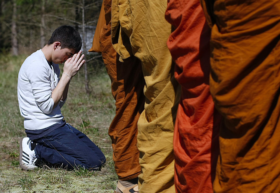 Photo - Adisorn Gronski, left, prays while monks from the Atammayatarama Buddhist Monastery in Woodinville chant for victims of the deadly mudslide in Oso, Wash., Tuesday, April 1, 2014, near a road block in Oso. The March 22 mudslide destroyed the rural mountainside community northeast of Seattle. (AP Photo/The Herald, Sofia Jaramillo) MANDATORY CREDIT.