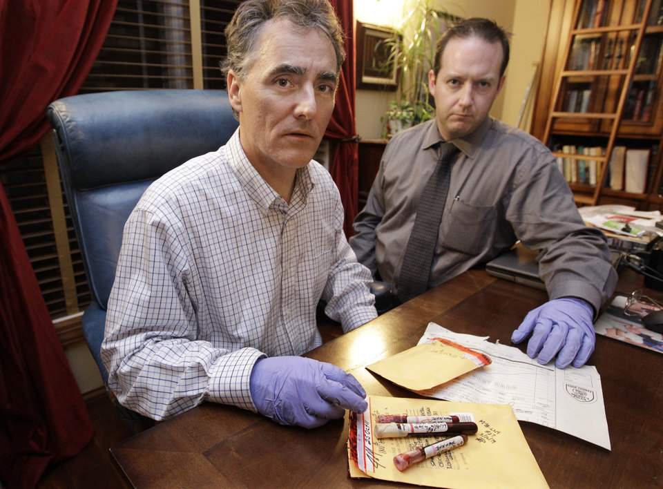 Photo - In this photo taken Friday, Nov. 30, 2012, in Chicago, Cook County Sheriff Tom Dart, left, and sheriff's detective Jason Moran are photographed with three recently discovered vials of mass murderer John Wayne Gacy's blood. The sheriff's office is creating DNA profiles from the blood of Gacy and other executed killers and putting them in a national DNA database of profiles created from blood, semen, or strands of hair found at crime scenes and on the bodies of victims. What they hope to find is evidence that links the long-dead killers to the coldest of cold cases and prompt authorities in other states to submit the DNA of their own executed inmates and maybe evidence from decades-old crime scenes to help them solve their own cases. (AP Photo/M. Spencer Green)