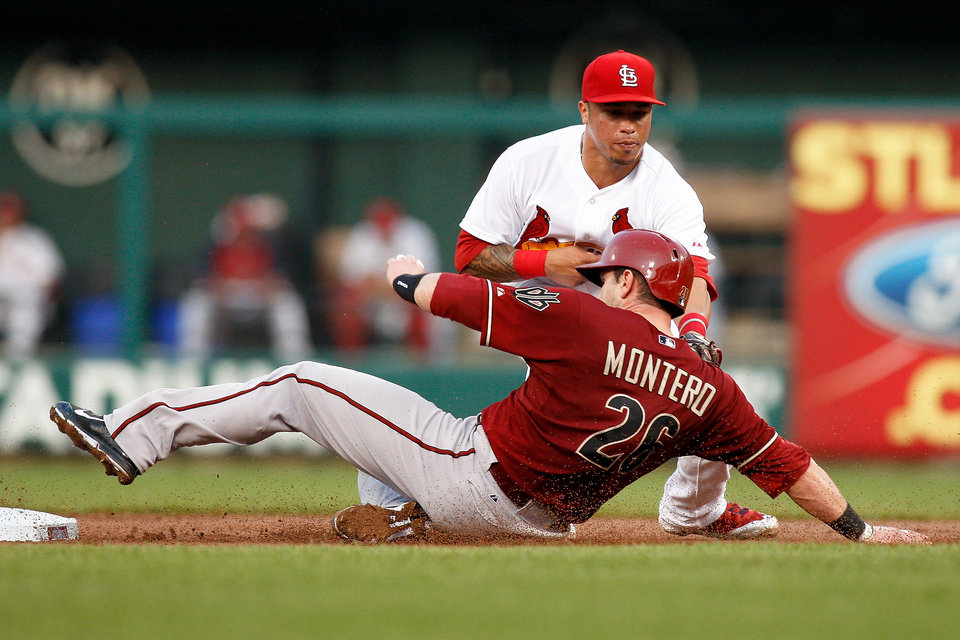 Photo - Arizona Diamondbacks' Miguel Montero is tagged out by St. Louis Cardinals second baseman Kolten Wong while attempting to steal second base during the second inning of a baseball game Wednesday, May 21, 2014, in St. Louis. (AP Photo/Scott Kane)