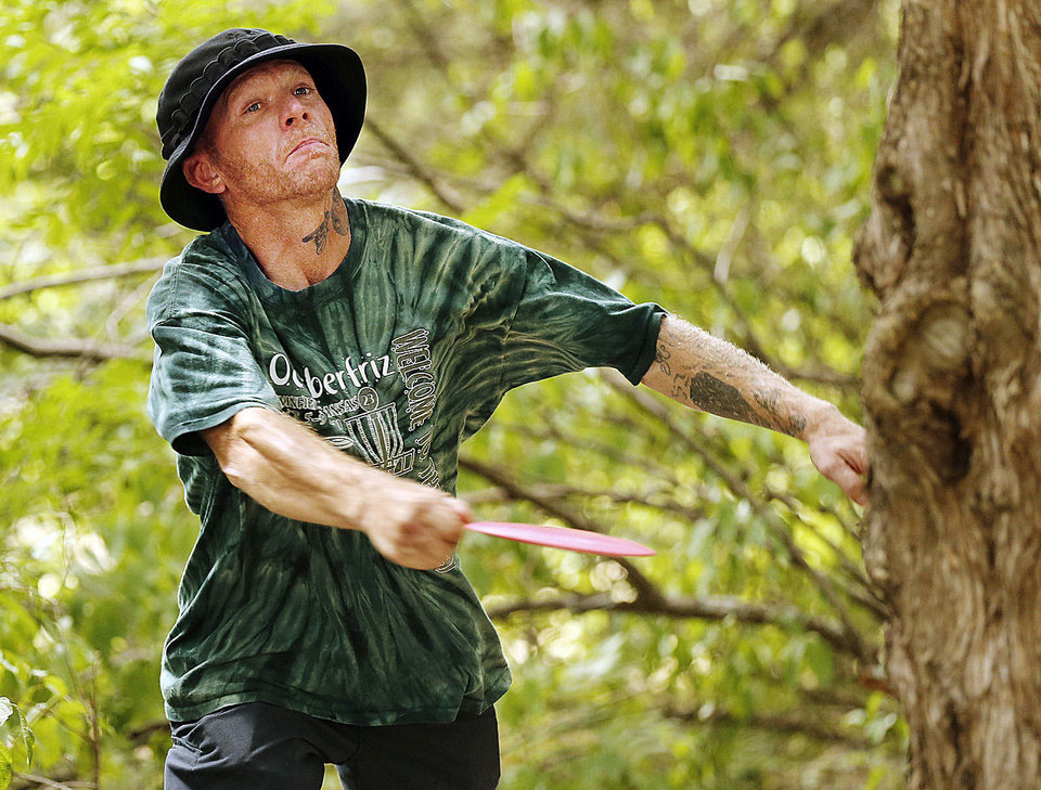 Photo - Jack Morrow, of Moore, throws a disc from a tee Saturday during the Kenneth Brent Edwards Memorial disc golf tournament in Norman. Photos by Steve Sisney, The Oklahoman