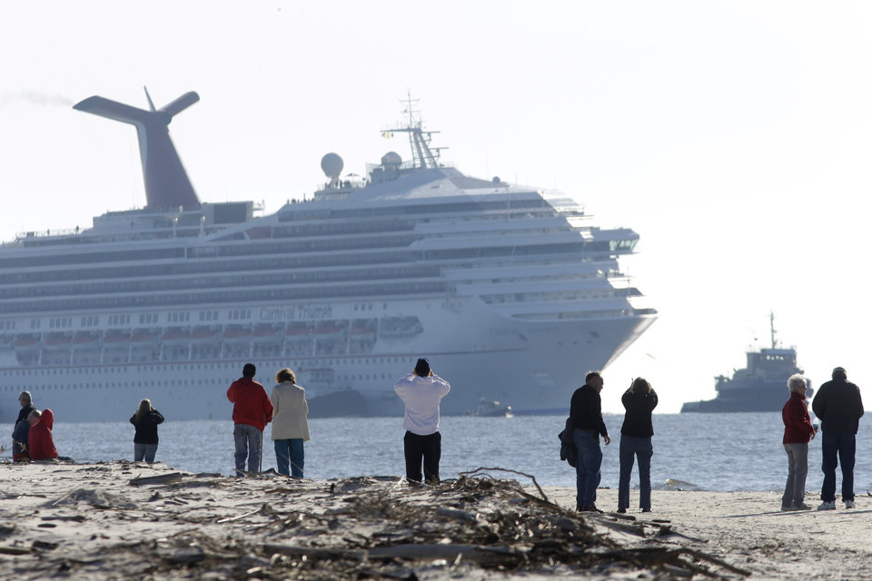 Photo - People on Spanish Fort watch as a disabled Carnival Lines cruise ship is towed to harbor off Mobile Bay, Ala., Thursday, Feb. 14, 2013. The ship with more than 4,200 passengers and crew members has been idled for nearly a week in the Gulf of Mexico following an engine room fire. (AP Photo/Gerald Herbert)