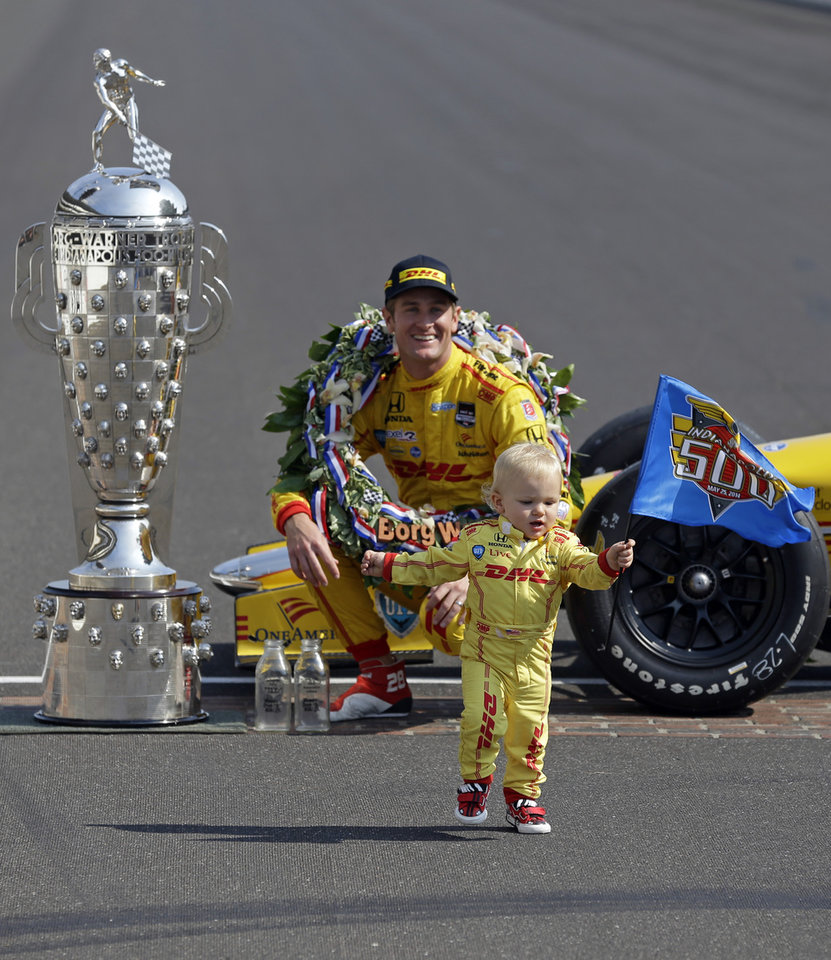 Photo - Indianapolis 500 champion Ryan Hunter-Reay watch as his son Ryden walks away with an Indy 500 flag as he poses during the traditional winners photo session on the start/finish line at the Indianapolis Motor Speedway in Indianapolis, Monday, May 26, 2014.  Hunter-Reay won the 98th running of the Indianapolis 500 IndyCar auto race on Sunday. (AP Photo/Michael Conroy)