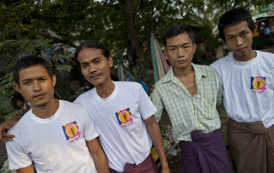 Photo - In this photo taken on April 4, 2013, Wai Phyo, second from left, stands for a photograph with some members of a 969 chapter at Kyimyindaing market in Yangon, Myanmar.
