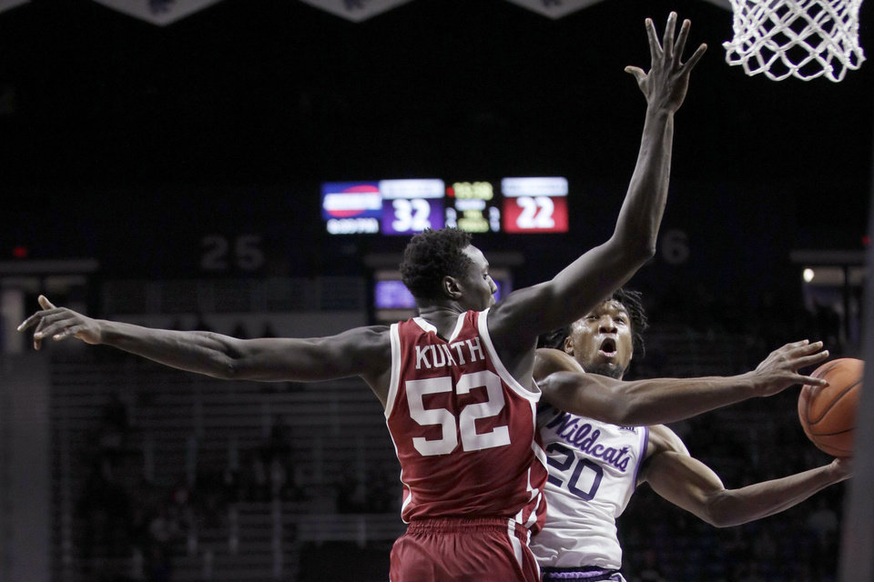 Photo - Kansas State forward Xavier Sneed (20) shoots while covered by Oklahoma forward Kur Kuath (52) during the second half of an NCAA college basketball game in Manhattan, Kan., Wednesday, Jan. 29, 2020. Kansas State won 61-53. (AP Photo/Orlin Wagner)