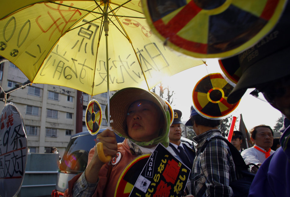 Photo - A protester holds an umbrella with slogans written on during an anti-nuclear demonstration in Tokyo, Saturday, March 9, 2013. Gathering on a weekend ahead of the second anniversary of the March 11 quake and tsunami that sent Fukushima Dai-ichi plant into multiple meltdowns, demonstrators said they would never forget the world's worst nuclear catastrophe, and expressed alarm over the government's eagerness to restart reactors. (AP Photo/Junji Kurokawa)