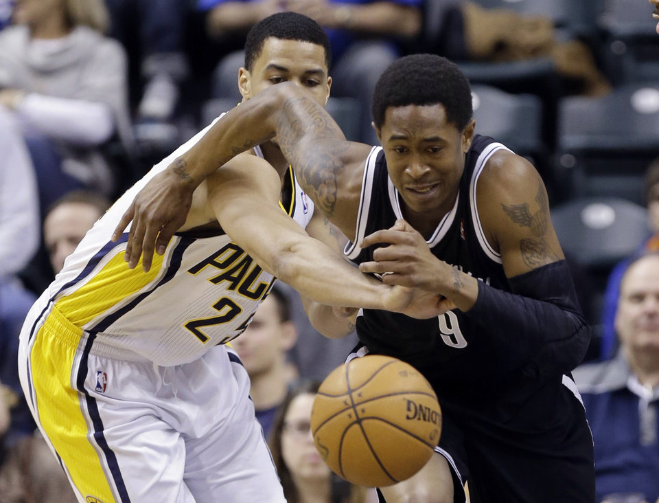 Photo - Brooklyn Nets guard MarShon Brooks , right is fouled by Indiana Pacers forward Gerald Green after making a steal in the first half of an NBA basketball game in Indianapolis, Monday, Feb. 11, 2013.  (AP Photo/Michael Conroy)