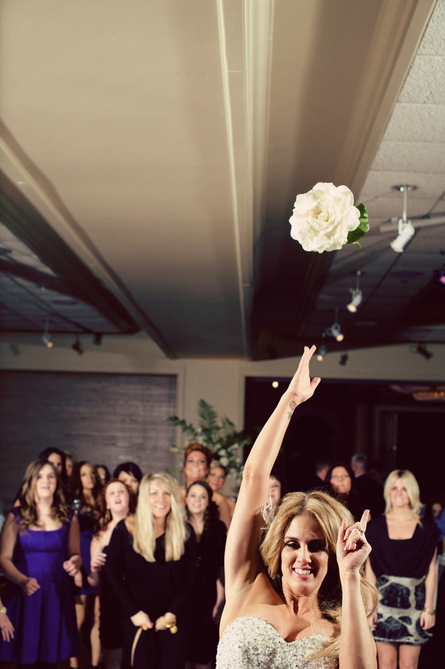 Photo - Malorie Gulikers throws her bouquet during her wedding. Photo by Traina Photography.
