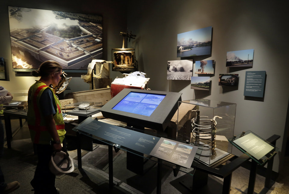 Photo - A Port Authority of New York and New Jersey worker views a display of the attack on the Pentagon at the National Sept. 11 Memorial Museum, Wednesday, May 14, 2014, in New York. The museum is a monument to how the Sept. 11 terror attacks shaped history, from its heart-wrenching artifacts to the underground space that houses them amid the remnants of the fallen twin towers' foundations. It also reflects the complexity of crafting a public understanding of the terrorist attacks and reconceiving ground zero.  (AP Photo)