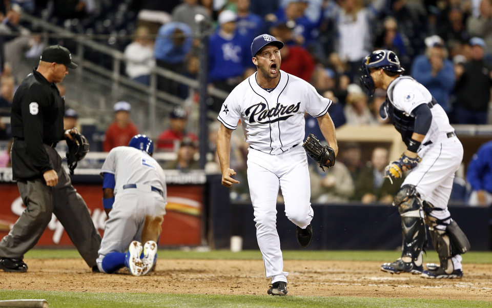 Photo - San Diego Padres relief pitcher Huston Street celebrates after Padres catcher Yasmani Grandal, right, tagged out Kansas City Royals' Alcides Escobar who was out trying to score from third on a pop out down the right field line during the ninth inning of a tied baseball game Tuesday, May 6, 2014, in San Diego. (AP Photo/Lenny Ignelzi)