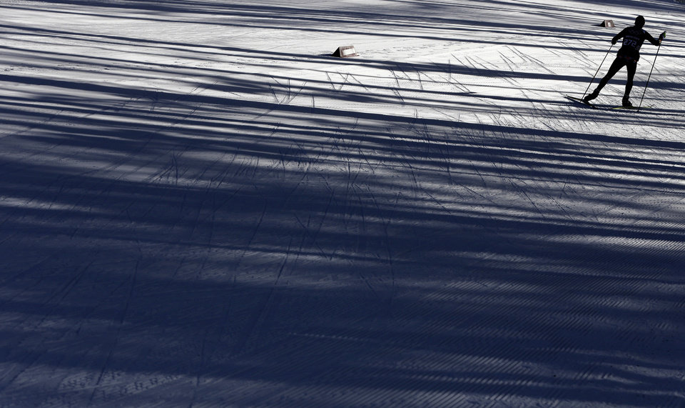 Photo - A skier is silhouetted during a biathlon training session at the 2014 Winter Olympics, Friday, Feb. 7, 2014, in Krasnaya Polyana, Russia. (AP Photo/Kirsty Wigglesworth)