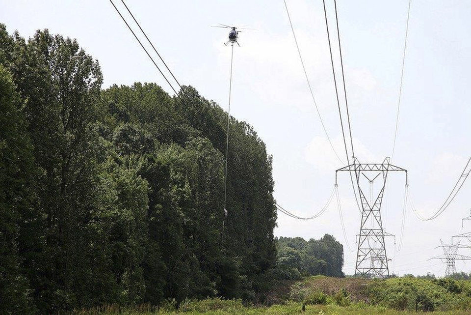 This July 8, 2013 photo provided by FirstEnergy shows a helicopter aerial saw trimming trees along a FirstEnergy transmission corridor in Doylestown, Ohio. Electric utility tree-trimmers have made their mark on the picturesque hillside where branches coming into contact with high-power lines helped set off a chain-reaction blackout stretching to Canada and the East Coast and fried household appliances 10 years ago. But the sound of chain saws isn\'t welcome to tree lovers who now see open skies where tall trees once shaded the power lines and the neighborhood. - AP Photo/HO, FirstEnergy