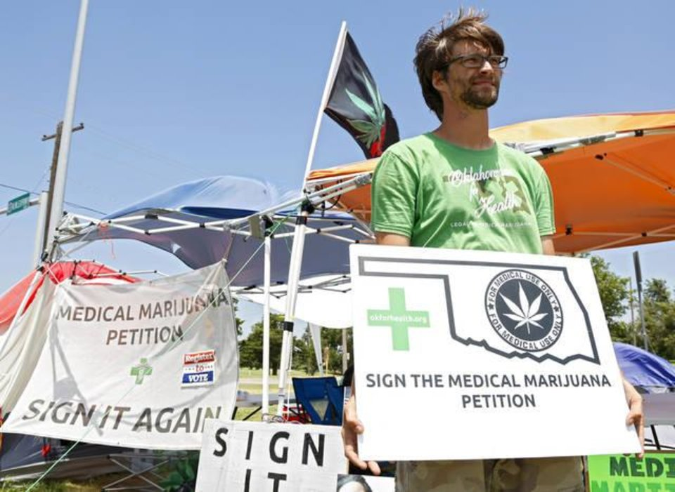 Photo - Frank Grove holds a sign for a portrait at Northwest Expressway and N Meridian Avenue in Oklahoma City, Wednesday, July 13, 2016. Grove and other volunteers are trying to get 66,000 signatures on a petition to get a statewide vote on for legalizing medical marijuana. Photo by Kurt Steiss, The Oklahoman