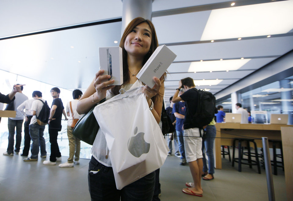 Photo -   A customer shows her new iPhone 5 at the Apple store in Hong Kong Friday, Sept. 21, 2012. Apple's Asian fans jammed the tech juggernaut's shops in Australia, Hong Kong, Japan and Singapore to pick up the latest version of its iPhone. (AP Photo/Kin Cheung)