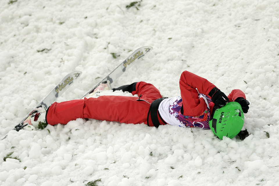 Photo - China's Li Nina lies in the snow after crashing on her final jump during the women's freestyle skiing aerials final at the Rosa Khutor Extreme Park, at the 2014 Winter Olympics, Friday, Feb. 14, 2014, in Krasnaya Polyana, Russia.(AP Photo/Andy Wong)