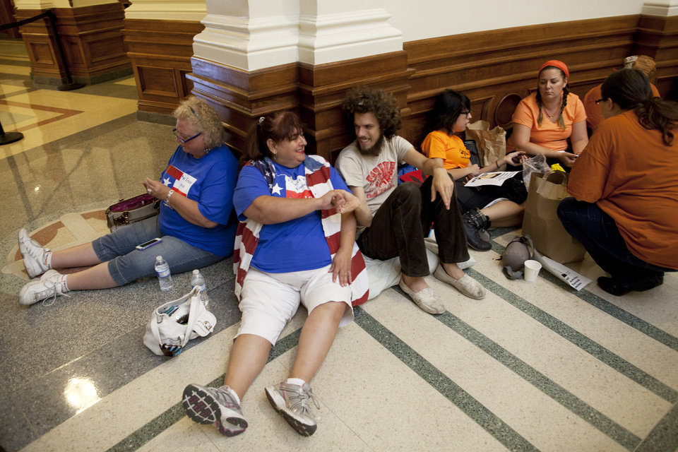 Kathy Morgan and Austin Smith introduce themselves while waiting in line to enter the Senate Gallery in the Texas State Capitol in Austin, Texas on Friday, July 12, 2013. The Texas Senate's leader, Lt. Gov. David Dewhurst, has scheduled a vote for Friday on the same restrictions on when, where and how women may obtain abortions in Texas that failed to become law after a Democratic filibuster and raucous protesters were able to run out the clock on an earlier special session. (AP Photo/Tamir Kalifa)