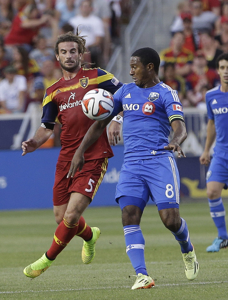 Photo - Montreal Impact's Patrice Bernier (8) and Real Salt Lake's Kyle Beckerman (5) battle for the ball in the first half during an MLS Soccer game on Thursday, July 24, 2014, in Sandy, Utah. (AP Photo/Rick Bowmer)