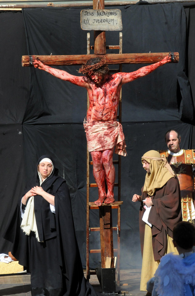 Photo - Portraying Jesus Christ a man takes part in a Way of the Cross procession, at the St. Isidoro Agricola church in Palermo, Sicily, Friday, April 18, 2014. Holy Week commemorates the last week of the earthly life of Jesus Christ culminating in his crucifixion on Good Friday and his resurrection on Easter Sunday. (AP Photo/Alessandro Fucarini)
