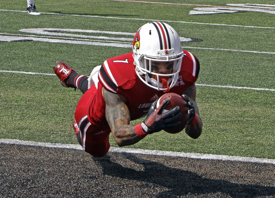 Photo - Louisville wide receiver Damian Copeland (7) makes a touchdown catch at the goal line in the first quarter of an NCAA college football game in Louisville, Ky., Sunday, Sept. 1, 2013 against Ohio University. (AP Photo/Garry Jones)