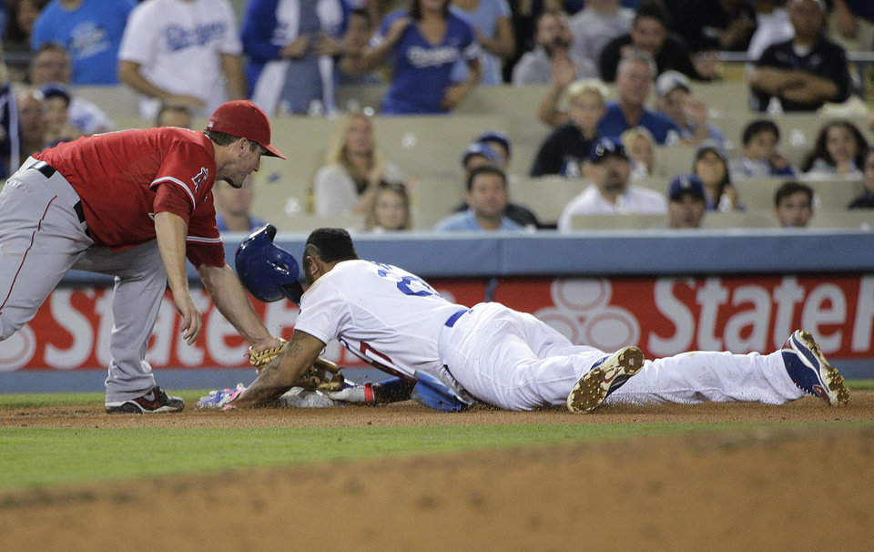 Photo - Los Angeles Dodgers' Matt Kemp safely takes third base as Los Angeles Angels third baseman David Freese applies a late tag, following a throwing error as Kemp stole second during the sixth inning of a baseball game on Tuesday, Aug. 5, 2014, in Los Angeles. (AP Photo/Jae C. Hong)