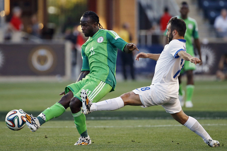 Nigeria forward Victor Moses, left, kicks the ball away from Greece midfielder Ioannis Fetfatzidis during the first half of an an international friendly soccer match, Tuesday, June 3, 2014, in Chester, Pa. (AP Photo/Matt Slocum)