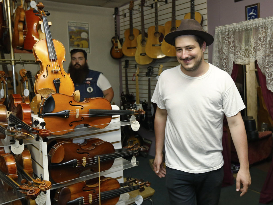 Photo - In this Sept. 5, 2013, photo Marcus Mumford, of the band Mumford & Sons, walks through Byron Berline's Double Stop Fiddle Shop in Guthrie,, Okla. The population of the small Oklahoma town is expected to quadruple this weekend as people come to watch the British folk rock band on the second stop of the Mumford & SonsÂ' Gentlemen of the Road concert series in Guthrie. (AP Photo/Sue Ogrocki) ORG XMIT: OKSO101