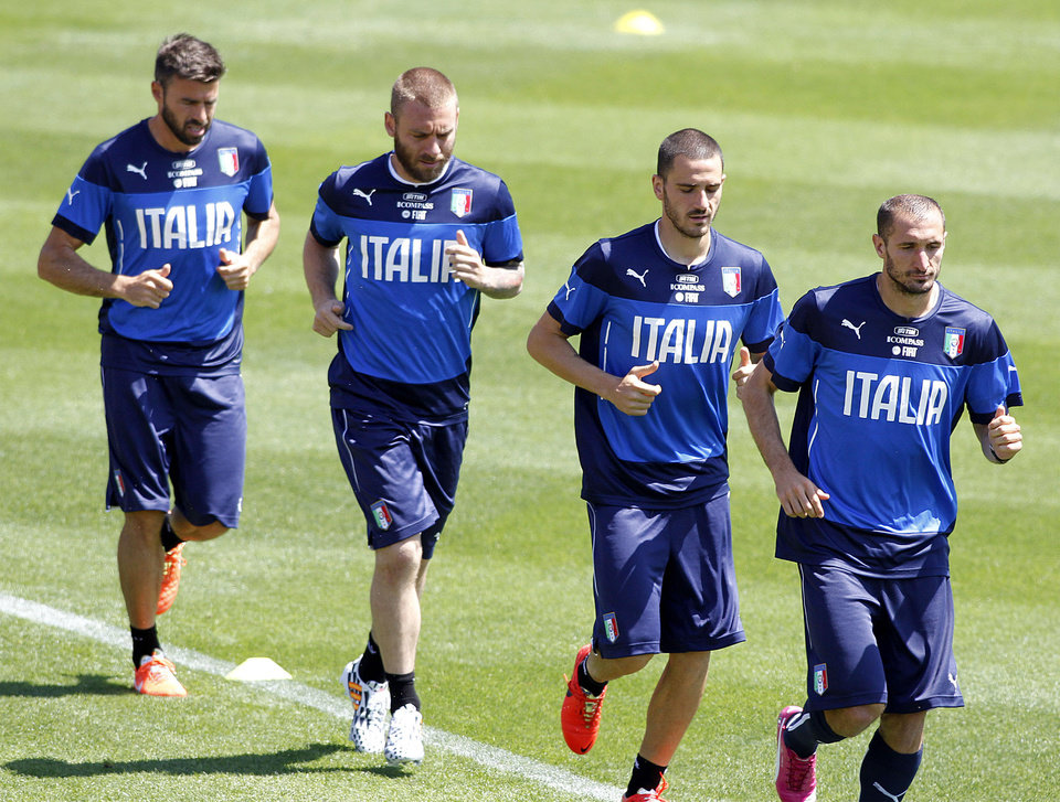 Photo - From left, Andrea Barzagli, Daniele De Rossi, Leonardo Bonucci and Giorgio Chiellini warm up during a training session in Coverciano training complex, in Florence, Italy, Tuesday, May 20 , 2014,   Italy opened its World Cup training camp Monday with 31 players.  Coach Cesare Prandelli needs to trim his squad to 23 players by June 2.  In Brazil, Italy is in Group D with England, Uruguay and Costa Rica. (AP Photo/Fabrizio Giovannozzi)