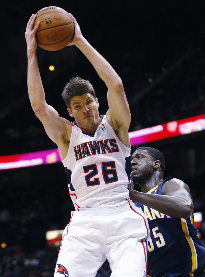 Photo - Atlanta Hawks shooting guard Kyle Korver (26) grabs a rebound in front of Indiana Pacers center Roy Hibbert (55) in the first  half of an NBA basketball game, Tuesday, Feb. 4, 2014, in Atlanta. (AP Photo/John Bazemore)