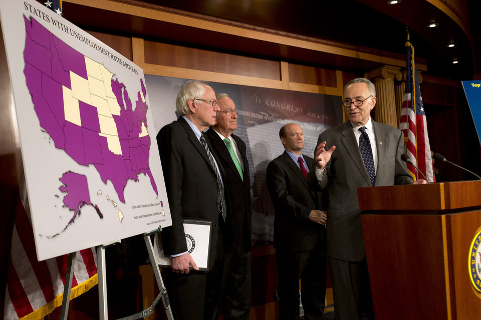 "FILE- In this Dec. 6, 2012, photo, Sen. Charles Schumer, D-N.Y., right, accompanied by from left, Sen. Bernard Sanders, I-Vt., Sen. Tom Harkin, D-Iowa, and Sen. Chris Coons, D-Del., gestures during a news conference the possibility of Americans abruptly their jobless benefits at the of the year on Capitol Hill in Washington,  Hovering in the background of the ""fiscal cliff"" debate is the prospect of 2 million people losing their unemployment benefits four days after Christmas. (AP Photo/Jacquelyn Martin)"