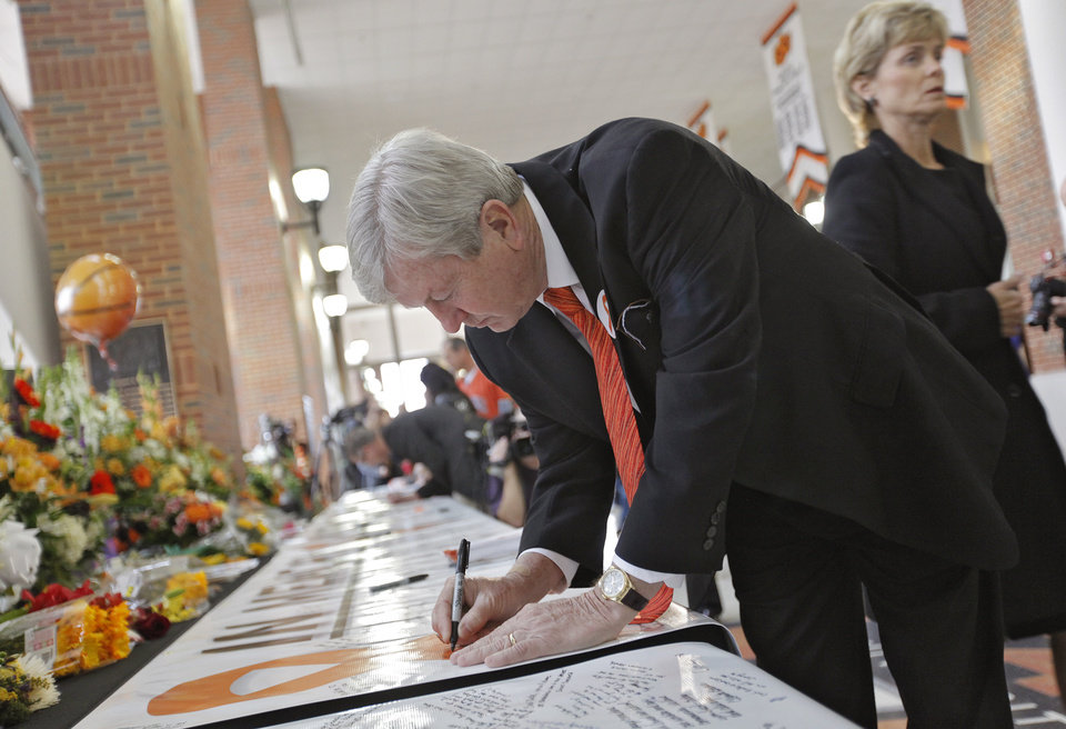 Photo - Texas A&M women's basketball coach Gary Blair signs the memory banner during the memorial service for Oklahoma State head basketball coach Kurt Budke and assistant coach Miranda Serna at Gallagher-Iba Arena on Monday, Nov. 21, 2011 in Stillwater, Okla. The two were killed in a plane crash along with former state senator Olin Branstetter and his wife Paula while on a recruiting trip in central Arkansas last Thursday. Photo by Chris Landsberger, The Oklahoman