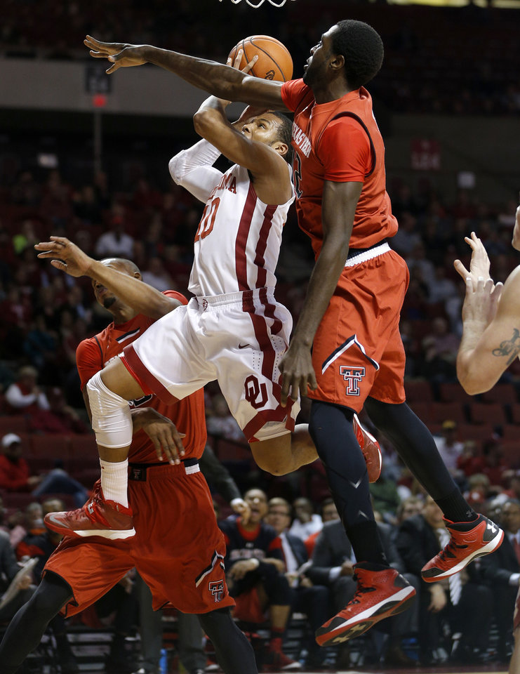 Photo - Oklahoma's Jordan Woodard (10) tries to get to the basket between Texas Tech's Jaye Crockett (30), at left, and Kader Tapsoba (12) during an NCAA college basketball game between the University of Oklahoma and Texas Tech University at the Lloyd Noble Center in Norman, Okla., Wednesday, Feb. 12, 2014. Photo by Bryan Terry, The Oklahoman