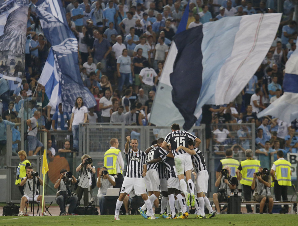 Juventus\' Carlos Tevez, hidden, is celebrated by teammates after scoring during the Italian Supercup soccer match against Lazio at the Rome Olympic stadium Sunday, Aug. 18, 2013. (AP Photo/Gregorio Borgia)