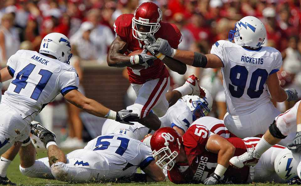 Photo - Oklahoma's DeMarco Murray (7) takes the ball up the middle through Air Force's Brady Amack (41), Zach Payne (51) and Rick Ricketts (90) during the first half of the college football game between the University of Oklahoma Sooners (OU) and the Air Force Falcons at the Gaylord Family - Oklahoma Memorial Stadium on Saturday, Sept. 18, 2010, in Norman, Okla.   Photo by Chris Landsberger, The Oklahoman