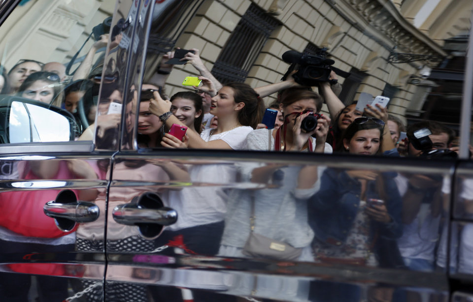 Photo - Fans are reflected on a van as they crowd outside an hotel where are believed to stay Kim Kardashian and Kanye West, in Florence, Italy, Saturday, May 24, 2014. Kim Kardashian and Kanye West will wed and host a reception at Florence's imposing 16th-century Belvedere Fort on May 24, according to a spokeswoman at the Florence mayor's office. The couple rented the fort, located next to Florence's famed Boboli Gardens, for 300,000 euros ($410,000) and a Protestant minister will preside over the ceremony. Belvedere Fort was built in 1590, believed using plans by Don Giovanni de' Medici. Located near the Arno River, it offers a panoramic view of Florence and the surrounding Tuscan hills. (AP Photo/Gregorio Borgia)